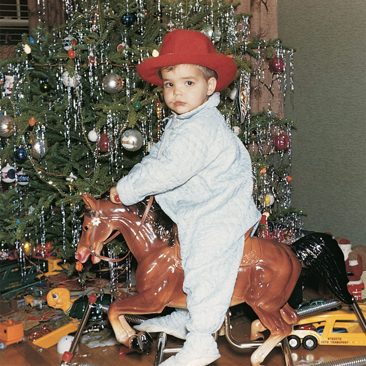 Boy riding a toy horse beside the Christmas tree