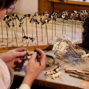 Artist painting small wooden cows