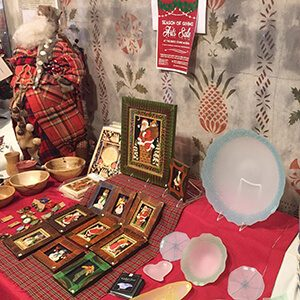 Table of plates and pictures at a holiday craft fair