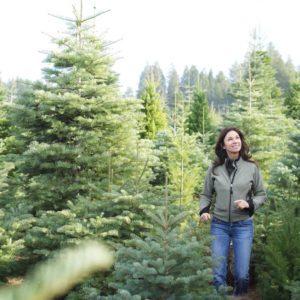 A woman wondering threw a christmas tree lot