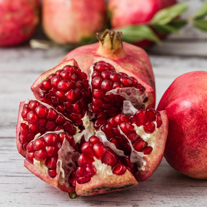 Half pomegranate and raw pomegranates on a white wooden background; Shutterstock ID 228369412