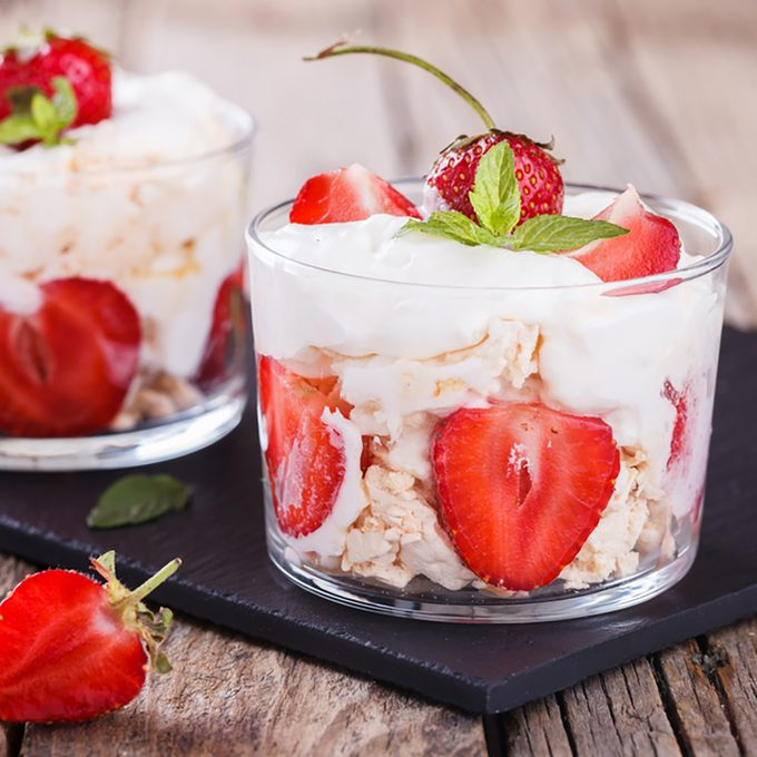 Eton Mess - Strawberries with whipped cream and meringue in a glass beaker.