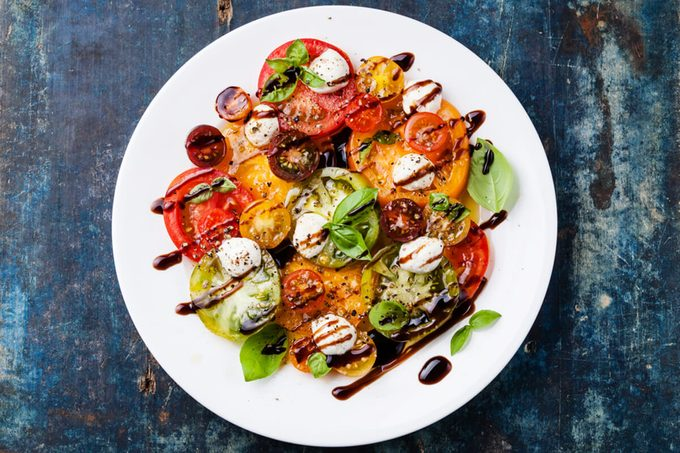 Colorful tomatoes salad with mozarella and balsamic vinegar on blue wooden background