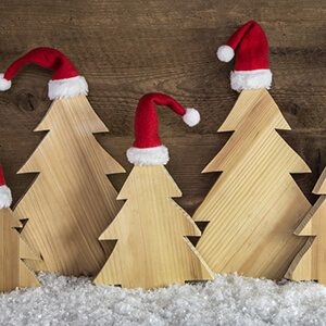 Funny wooden christmas background with trees and santa hats on snow.