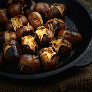 Heap of grilled edible chestnuts in cast iron skillet over dark wooden surface with textile napkin