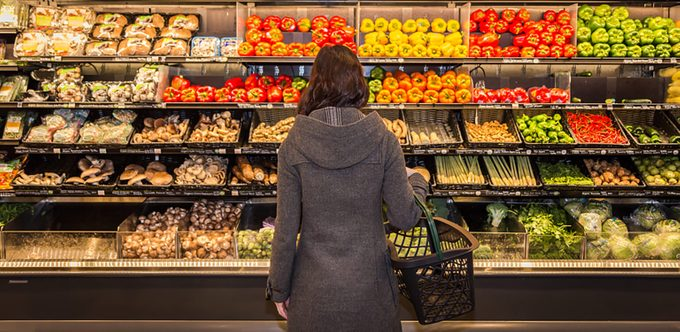 Woman standing in front of a row of produce in a grocery store.
