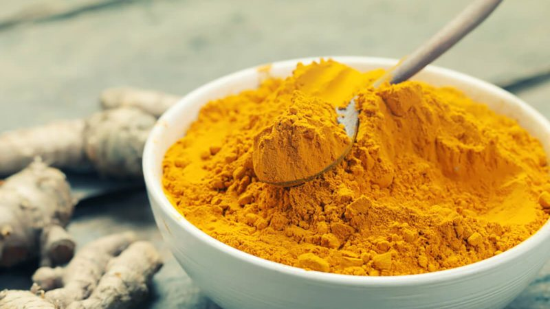 Turmeric powder and turmeric on wooden background