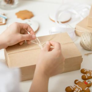 Close up of confectioner hands wrapping a simple kraft cardboard box.