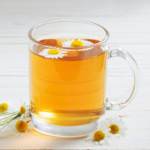 cup of chamomile tea on white wooden background