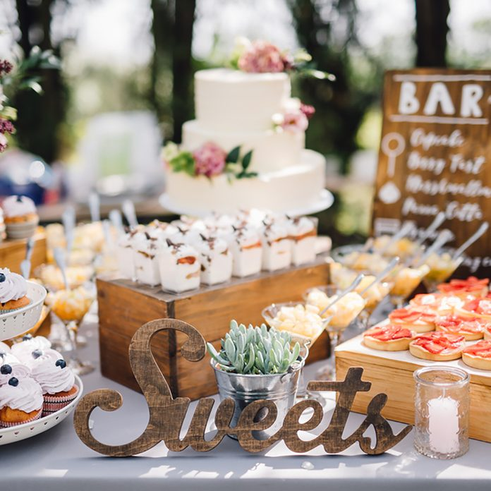 Handmade wooden Sweets sign standing in the middle of the table. Cupcakes, tarts, tartlets, pies and cakes on background. Wedding. Reception. Candy Bar; Shutterstock ID 638964427