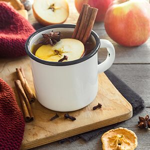 Hot drink of apple tea with cinnamon stick, star anise and clove.