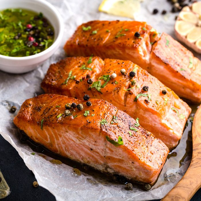 Delicious fried salmon fillet, seasonings on blue rustic concrete table. Cooked salmon steak with pepper, herbs, lemon, garlic, olive oil, spoon. Grilled fresh fish. Fish for healthy dinner. Close-up; Shutterstock ID 719333500