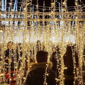 People walking through a maze of hanging Christmas lights