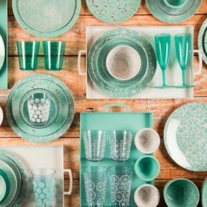 Teal cups, plates and bowls laying flat on a kitchen table