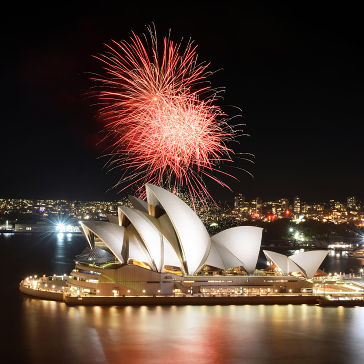 Fiery red fireworks light up the Sydney Opera House and Harbor in a brilliant display