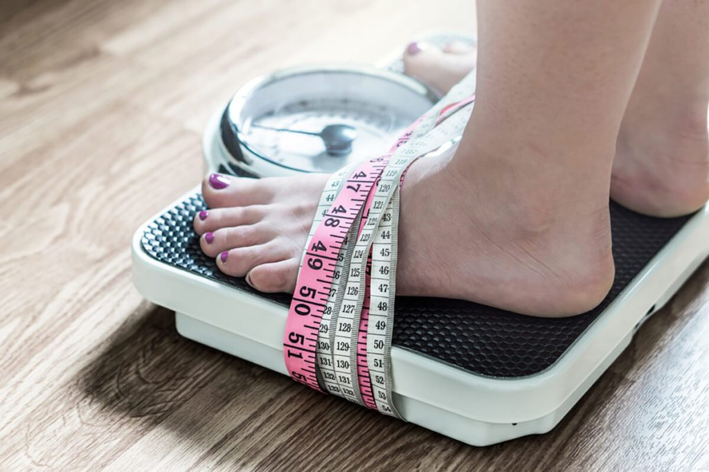 Feet tied up with measuring tape to a weight scale.