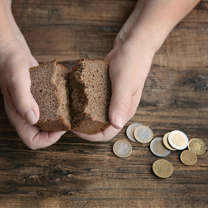Hands of senior woman with bread and coins on wooden background.