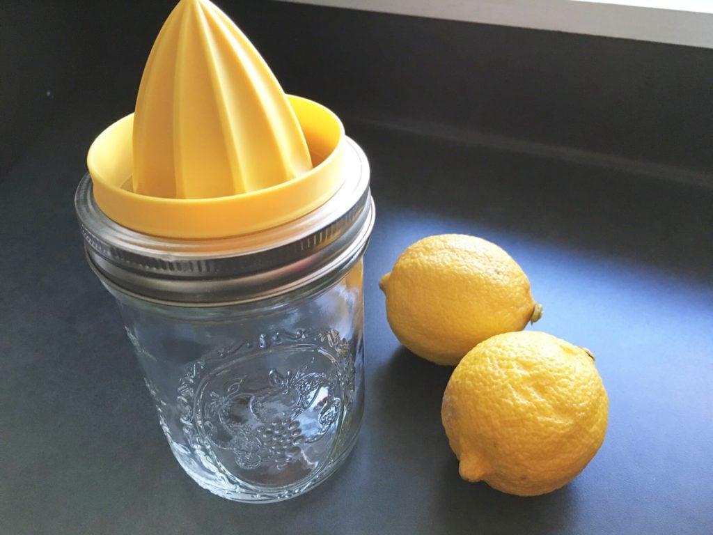 Mason jar juicer on a mason jar beside two lemons