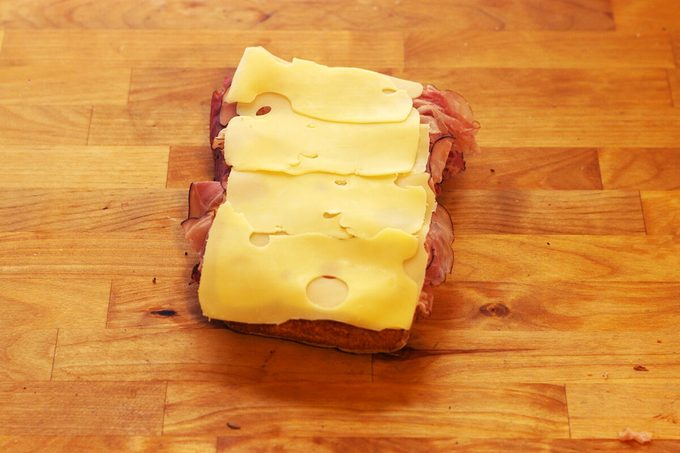Meat and cheese layered together on a slice of bread