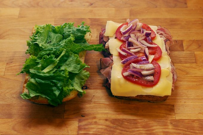 Two slices of bread one with meat, cheese and tomatoes and the other with lettuce
