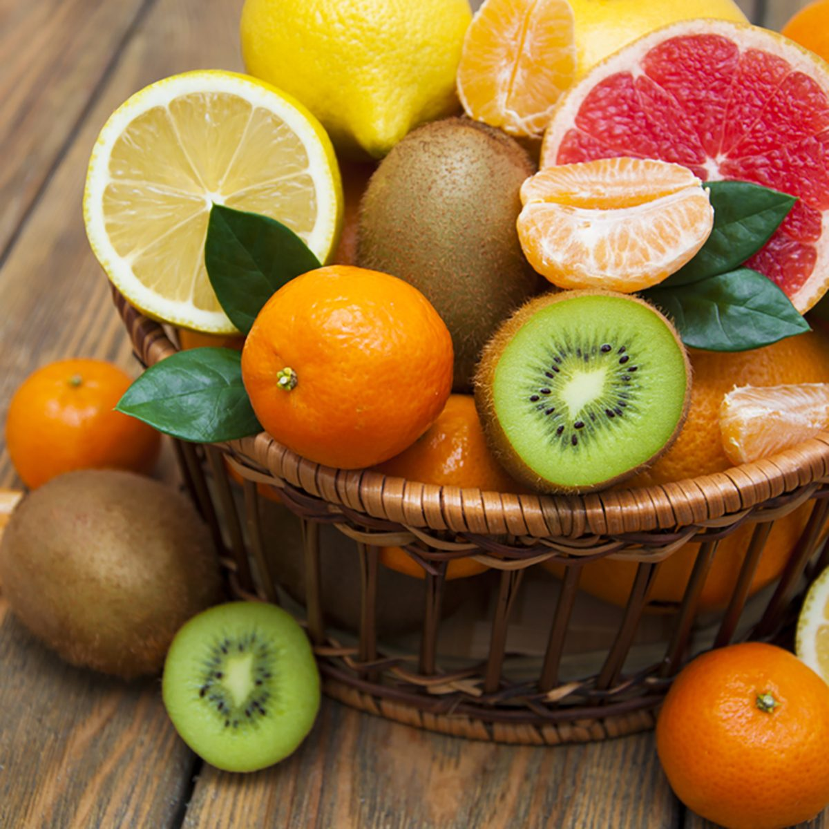 Fresh juicy citrus fruits in a basket on a wooden background