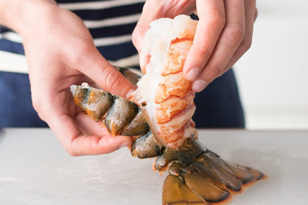 Person peeling back the shell from a lobster tail