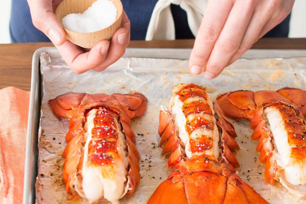 Person sprinkling salt over lobster tails on a baking sheet
