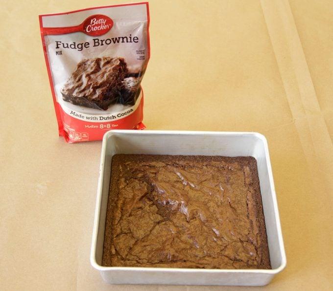 Betty Crocker brand brownies in a pan beside its packaging