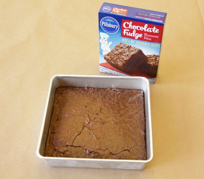 Pillsbury brand brownies in a pan beside its packaging