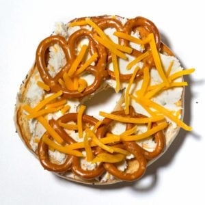 Bagel topped with; cream cheese; cheddar cheese; beer; ranch dressing mix; pretzels