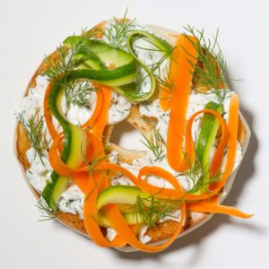 bagel topped with cream cheese; fresh dill; carrot; zuchinni