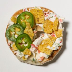 Bagel topped with; cream cheese; jalapeno peppers; red peppers; tortilla chips