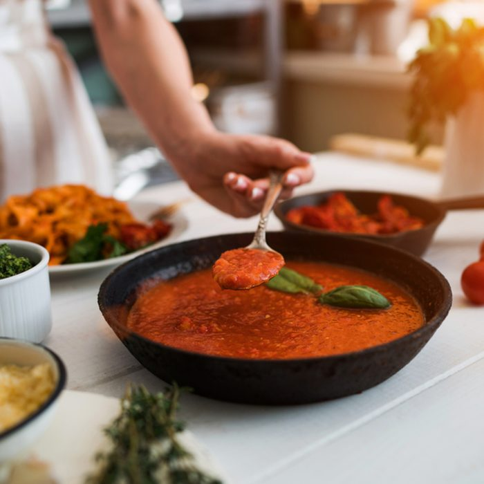 Woman making homemade pasta with tomato sous and cheese over old wooden table. Tomato, olive oil, spices, herbs, cheese, tomato sauce on a weathered wooden table in the summer sun's rays. Organic food; Shutterstock ID 1084753490; Job (TFH, TOH, RD, BNB, CWM, CM): TOH