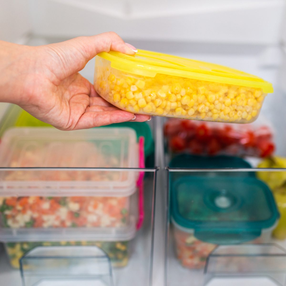Woman taking container with frozen corn from refrigerator.; Shutterstock ID 1154258860; Job (TFH, TOH, RD, BNB, CWM, CM): TOH