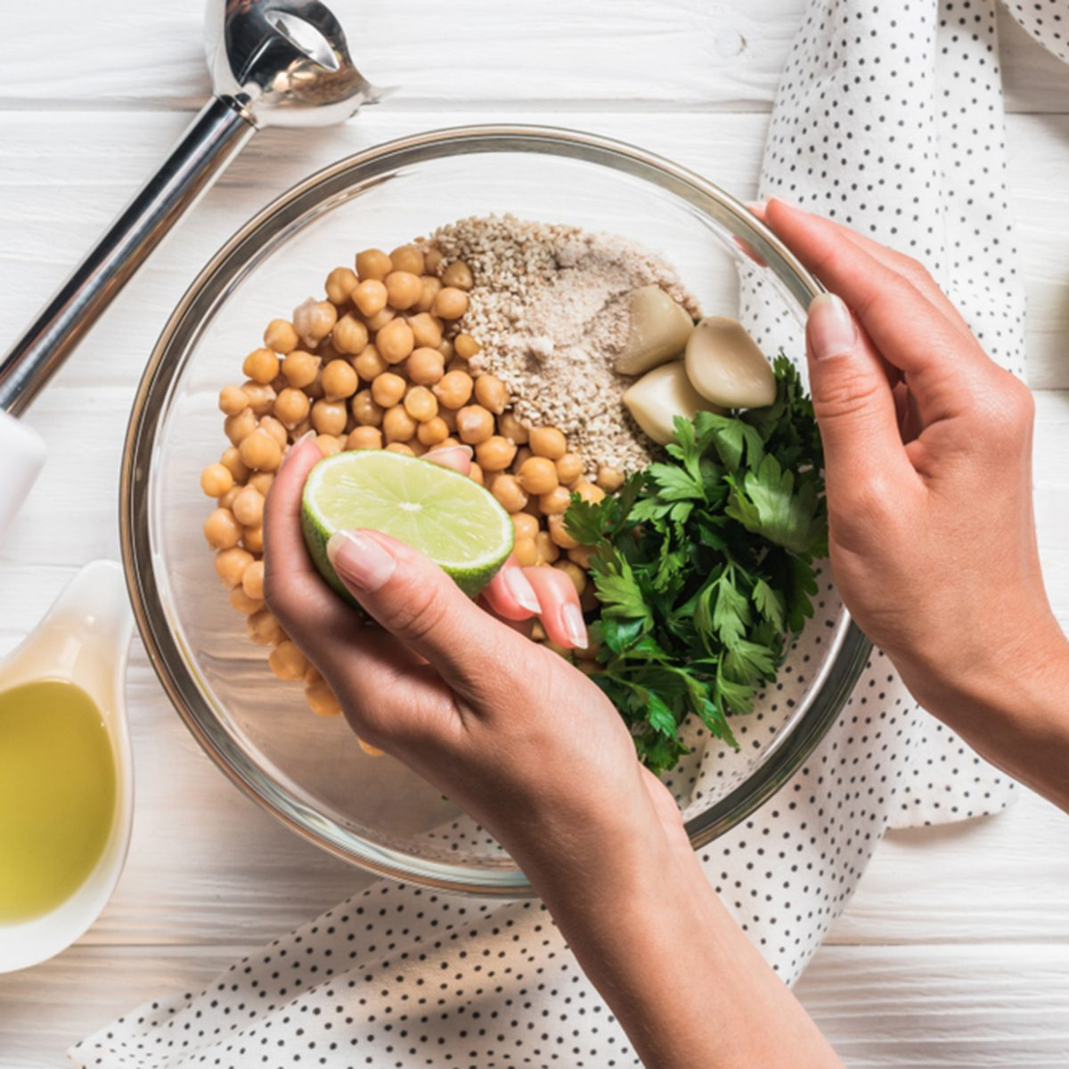 Cropped shot of woman, ingredients for hummus in bowl, olive oil and blender on wooden tabletop; Shutterstock ID 1161797650; Job (TFH, TOH, RD, BNB, CWM, CM): TOH