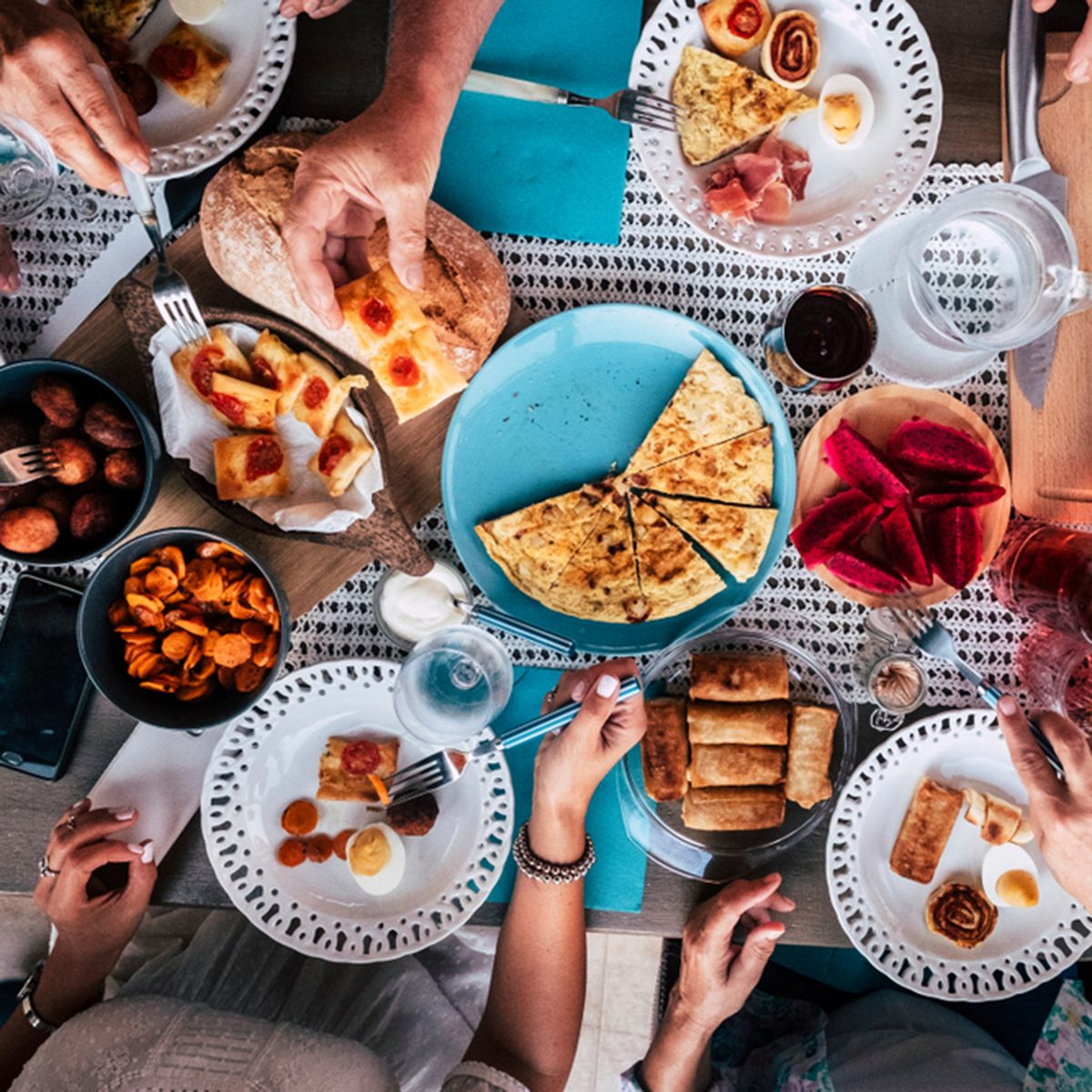 Above aerial view of group of friends having fun eating together at lunch or dinner with a table full of different and colorful food and technology mobile phone. mix of hands of caucasian people ; Shutterstock ID 1196986168; Job (TFH, TOH, RD, BNB, CWM, CM): TOH