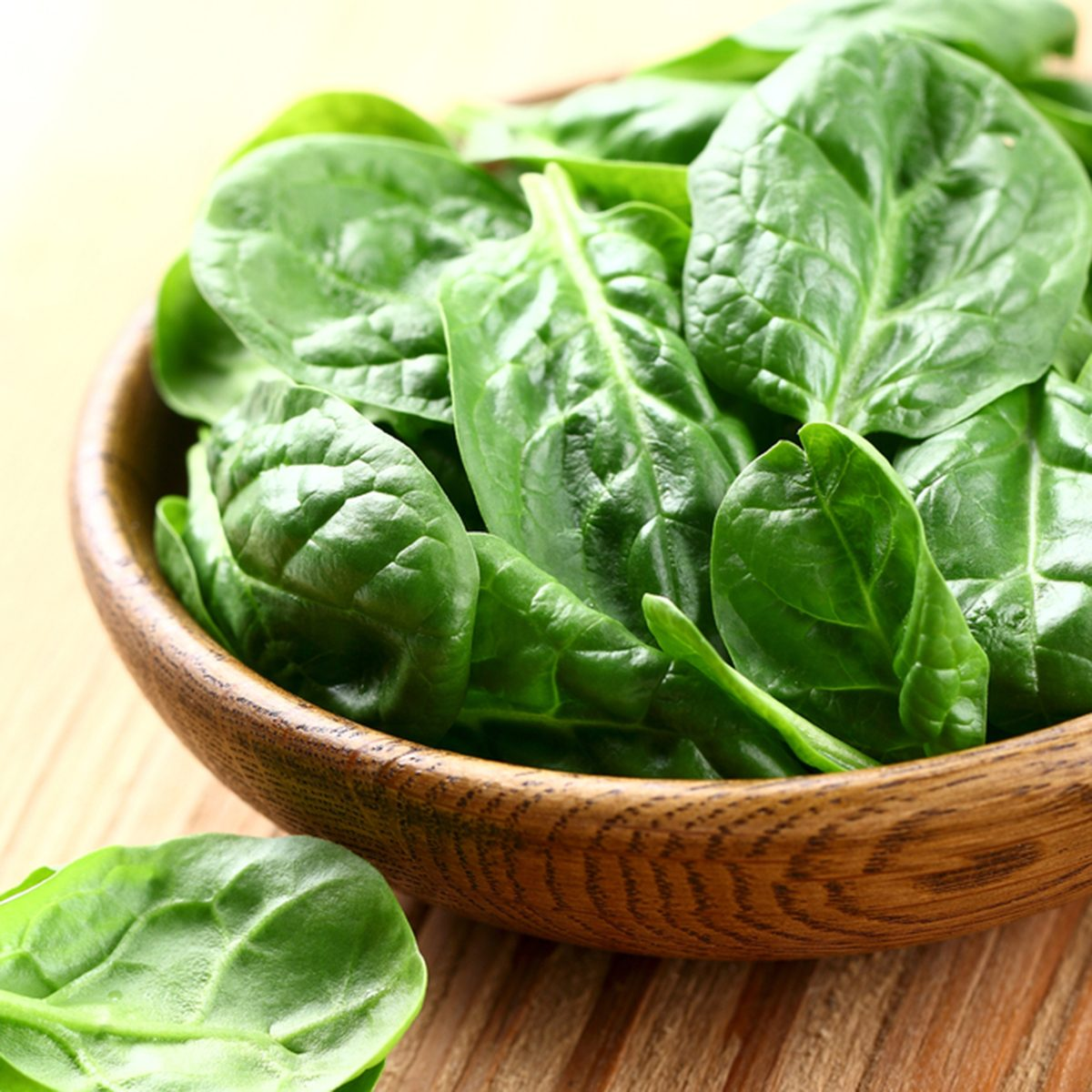 Young spinach in a wooden plate; Shutterstock ID 127762526