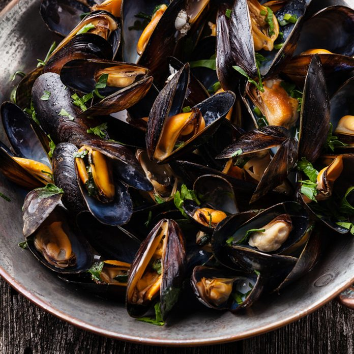 Boiled mussels in copper cooking dish on dark wooden background close up; Shutterstock ID 213081100