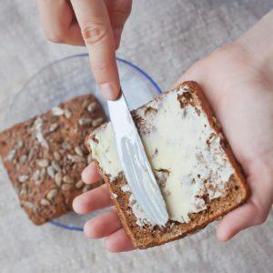 woman hand rubs butter on piece of rye bread