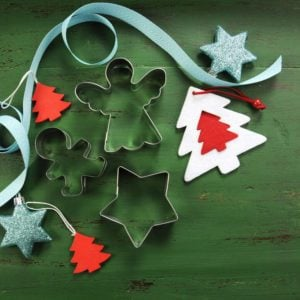 Christmas holiday background with red, white, festive decorations and cookie cutters against a vintage style dark green recycled wood background