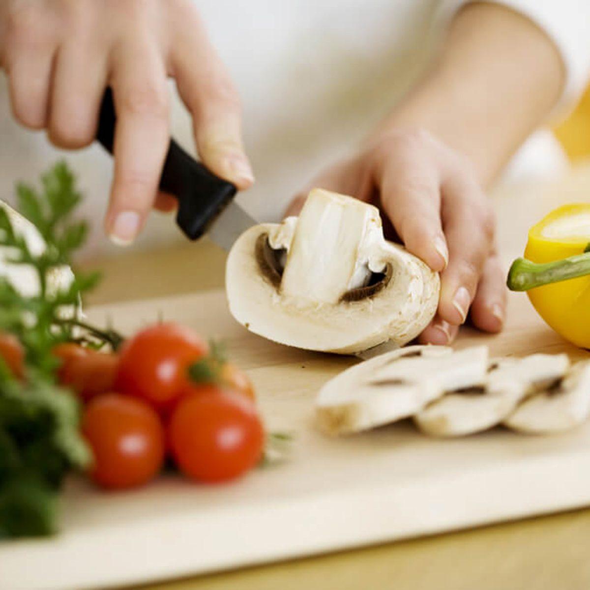 Person slicing mushroom