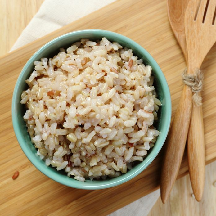 Organic Brown Rice in the bowl on the wooden table; Shutterstock ID 280020284