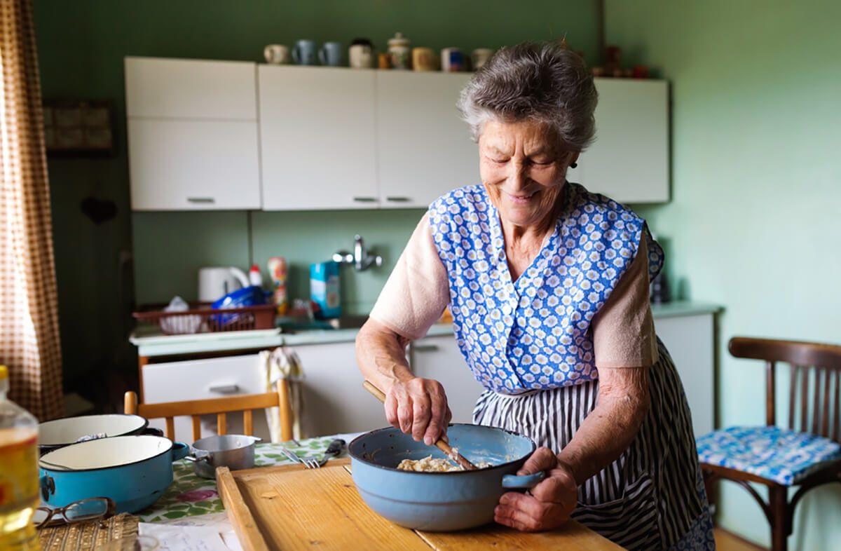 Senior woman baking pies in her home kitchen.