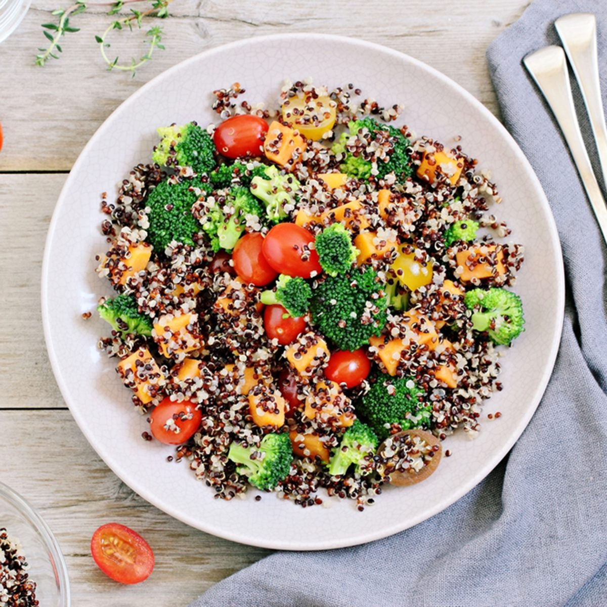 Quinoa salad with broccoli, sweet potatoes and tomatoes on a rustic wooden table. Three-color quinoa salad. Superfood and healthy eating concept. ; Shutterstock ID 380364796; Job (TFH, TOH, RD, BNB, CWM, CM): TOH