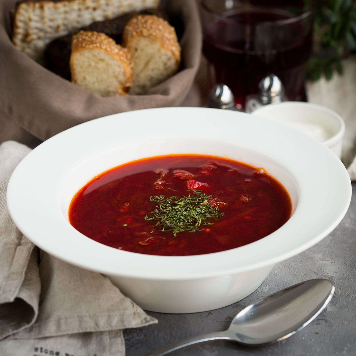 Vegetable soup with beetroot (borscht) on a rustic tablecloth
