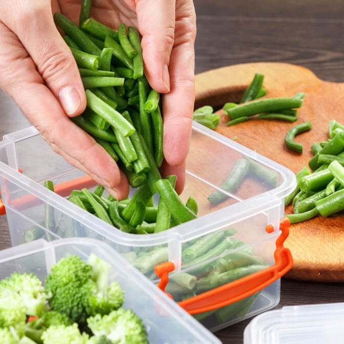 Person putting green beans into plastic container