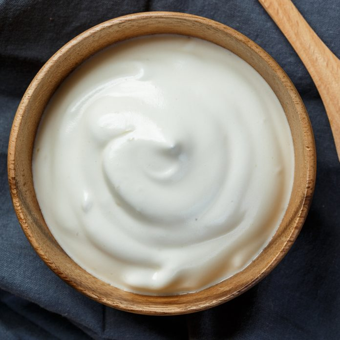 Homemade yogurt or sour cream in a wooden bowl; Shutterstock ID 515797933