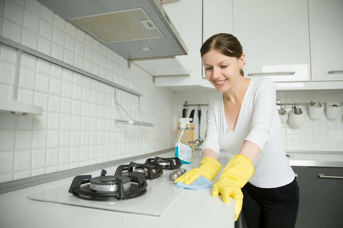 Young smiling woman wearing rubber protective yellow gloves cleaning the stove with a rag and spray