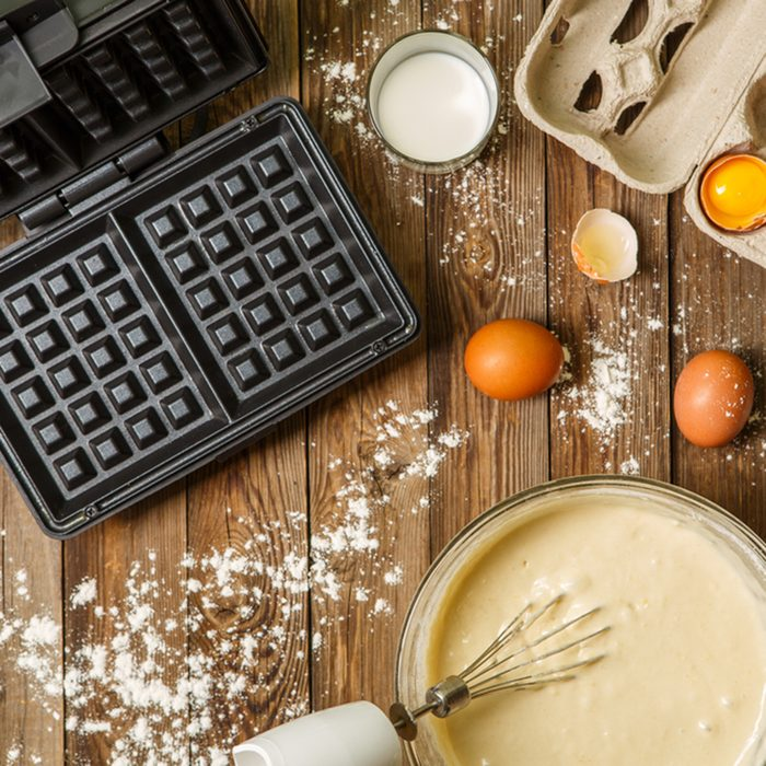 Making waffles at home - waffle iron, batter in bowl and ingredients - milk, eggs and flour. Cooking background.; Shutterstock ID 526047058; Job (TFH, TOH, RD, BNB, CWM, CM): TOH