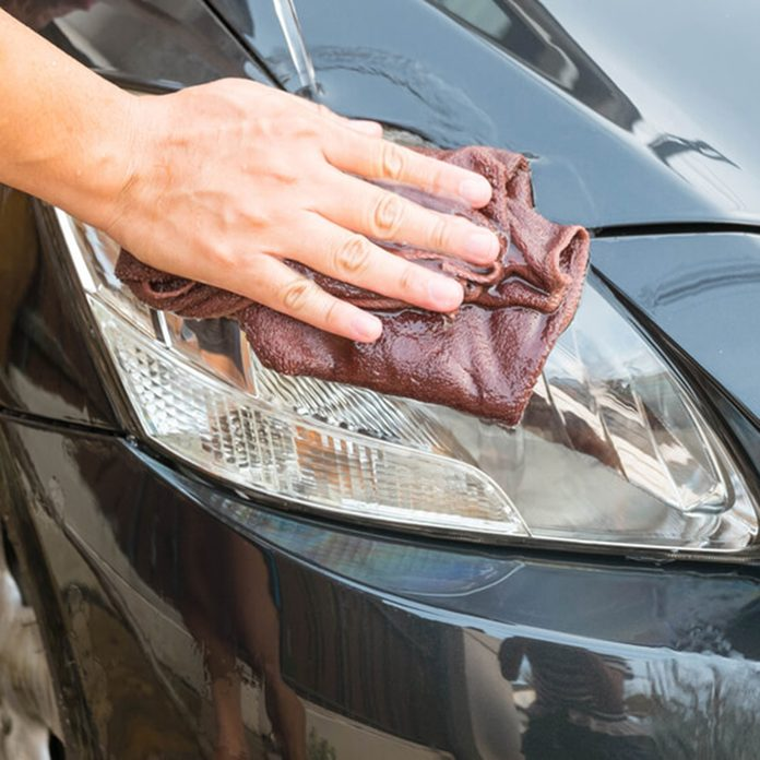 Person wiping cloth on car